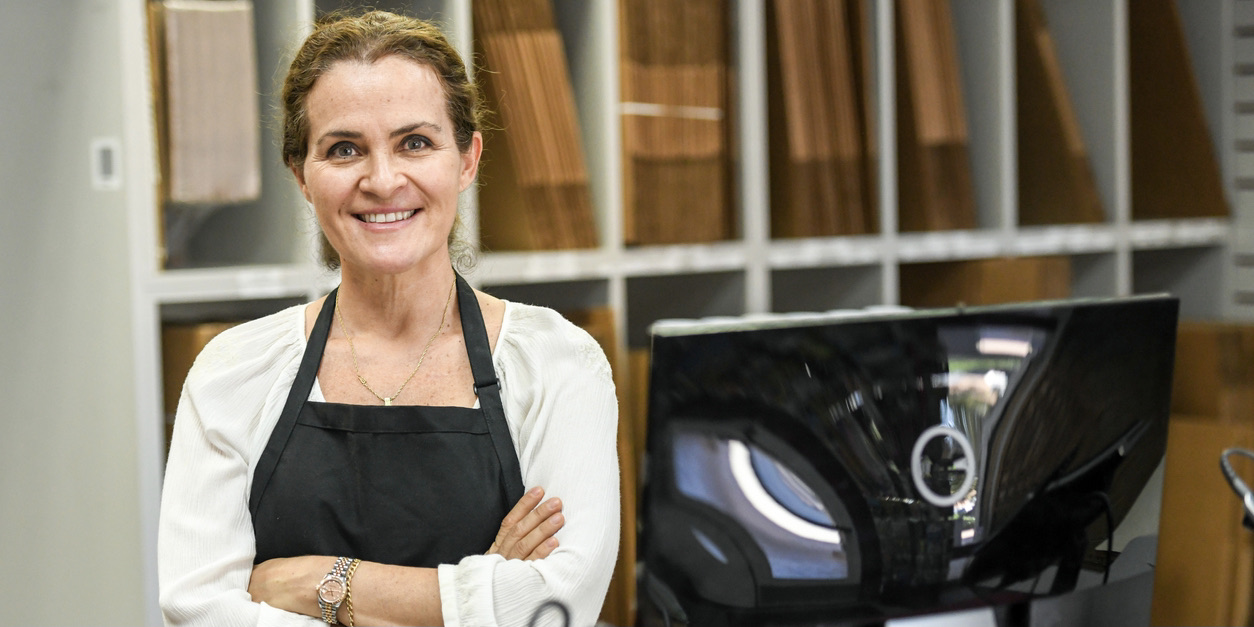 Middle aged woman standing behind counter of her business