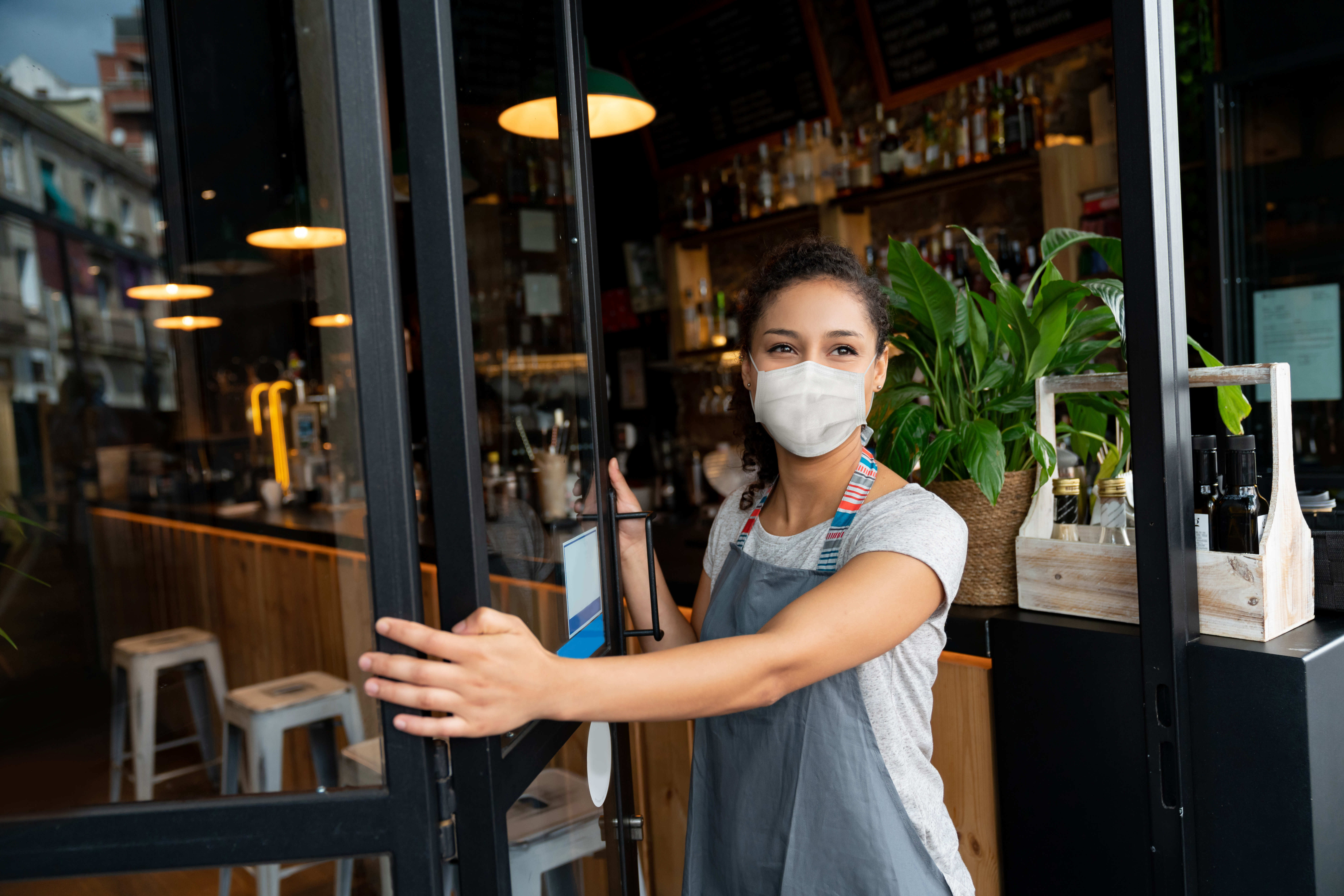 Masked woman reopening small business