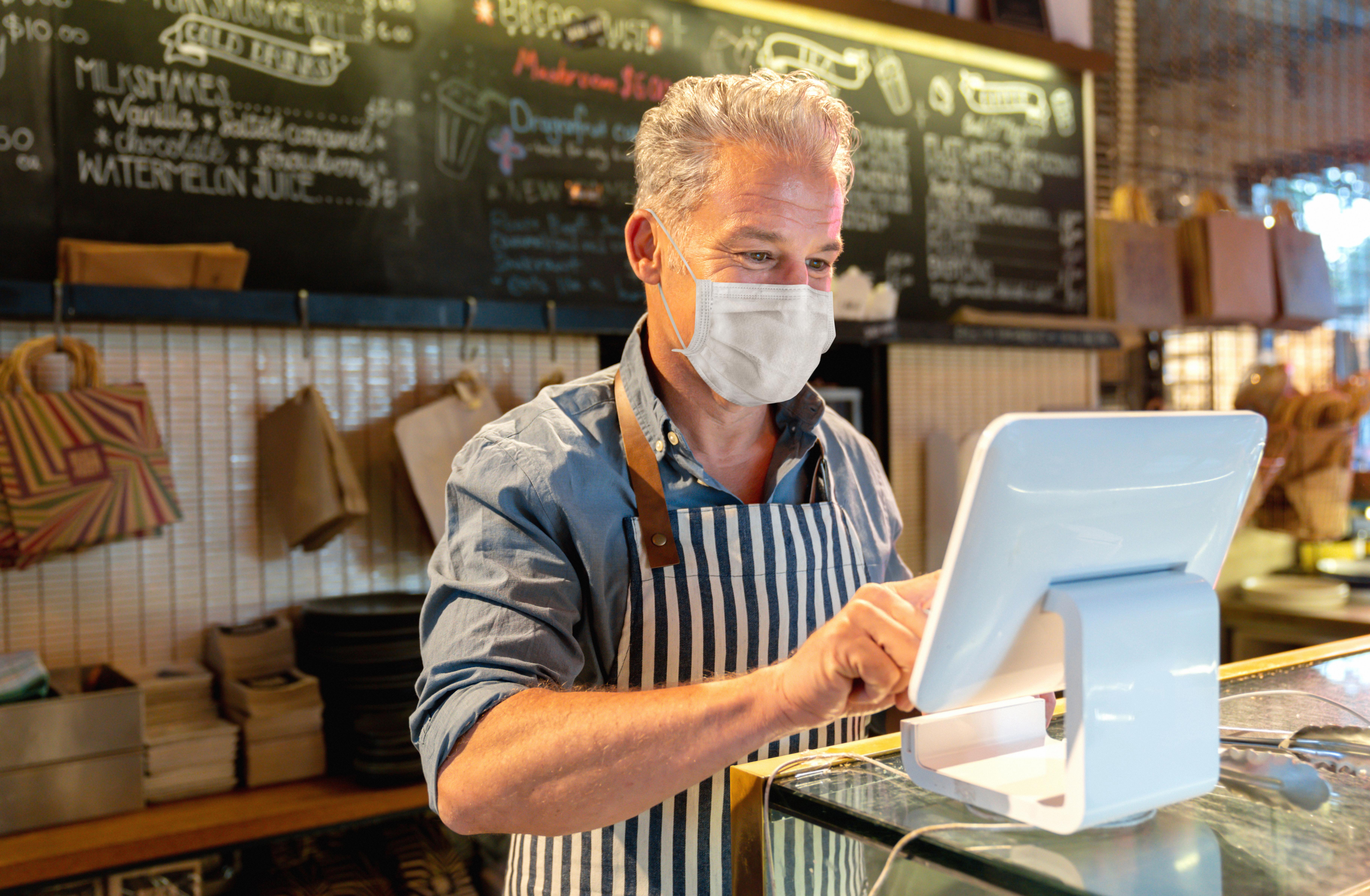 Middle-aged business owner in mask uses cash register tablet